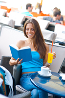 attractive girl reading book in coffee shop
